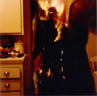 A man stands in the kitchen as he bursts into flame. He doesn't seem to be feeling any pain. Perhaps this has to do with all the medication bottles found along the counter. His eyes look at the viewer and sparkle from deep empty sockets. Flames erupt around him and burst from inside him. This is a scary image.