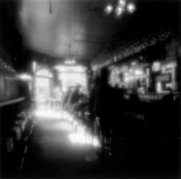 This is an misty old fashioned shot of a bar. It has ghostly looking people sitting on stools. they are ethereal transparent images. The light is filtering in through a window and falling on the bar. It looks like it could be anytime between 1930's to the present. The little lights are twinkling around the bar. While the people look like ghosts the overall feeling is warm and pleasant.