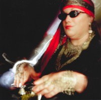 This is part of the Mystical Magical shoot. The model is decked out to tell fortunes with a crystal ball. Her blind eyes are covered by dark glasses.
