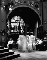 This is a shot of church during Christmas mass. It has a spiritual feeling. The people appear in different densities. Some are ghosting, some are solid and look like old fashioned daguerreotypes. There is a repetition of threes going on in the photo. There are three images of the priest on the alter as he gives his sermon. The trinity is an underlying theme.