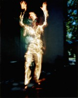 There is a guy peeking out from a darkened room to the sun lit blue sky. People no longer are solid entities to me unless I touch them. They mix with faults impressions I get for solid objects as I walk the streets of Sacramento. The reflected sound off a bush could be a person? or a spirit. To peek out the door of my studio is the very edge of perception. So I have mixed the surreal world that I have created in my studio looking into the real world outside.