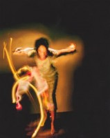 This is a Shamanistic image. It is an animal spirit portrayed by a dancer. It shows the intensity of the woman as if she were a bird swooping down on something. She looks like a real spitfire with flashes of neon lights around her.